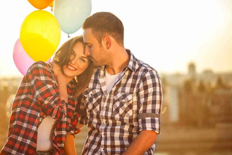 young couple posing with colorful balloons