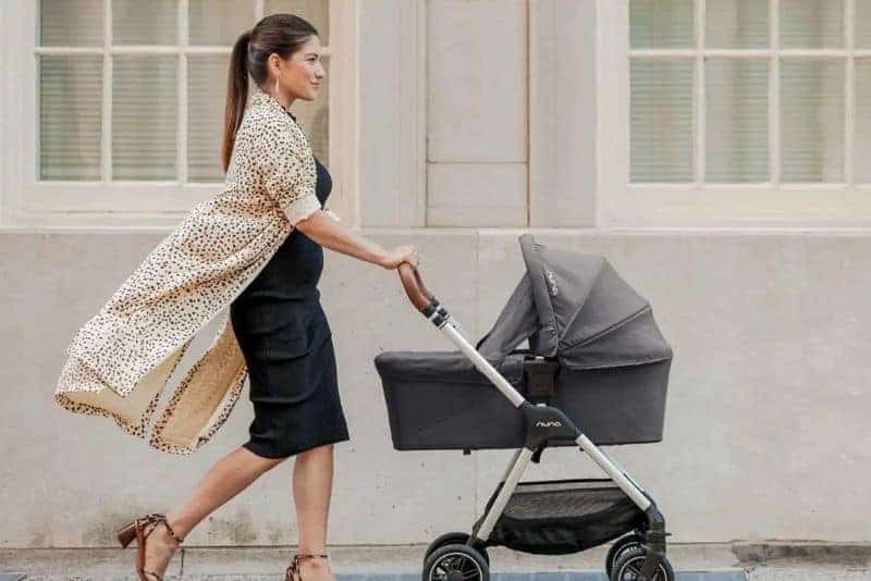 young mother pushing baby in a stroller