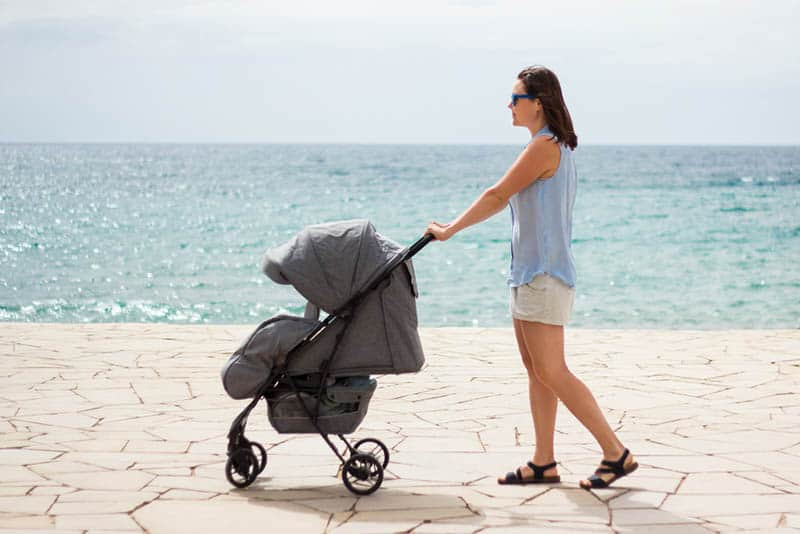 young mother walking with her baby in a stroller by the sea
