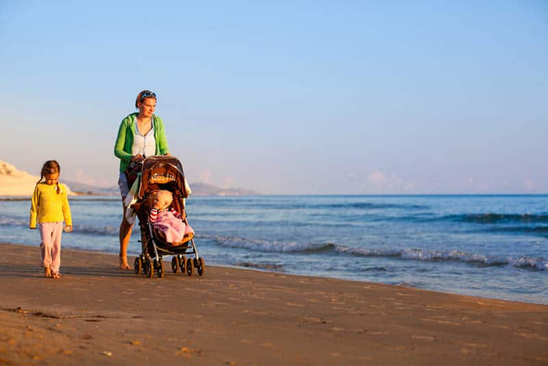 young mother walking with kids on the beach