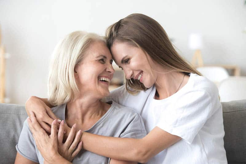 young woman hugging her smiling mother on the couch