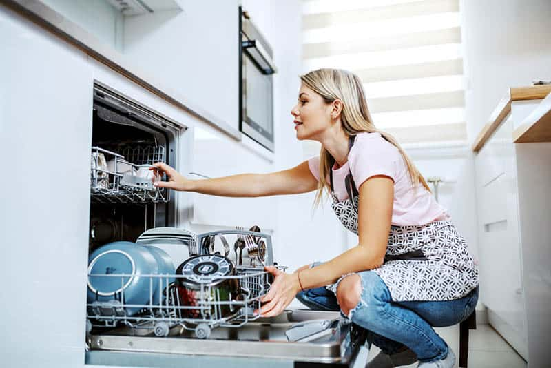 young woman pulling out dishes in a dishwasher