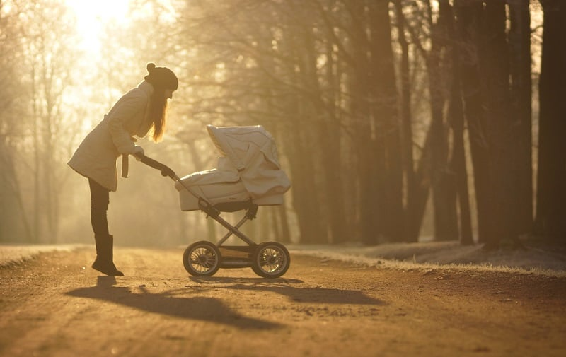 young woman with stroller during the winter