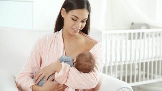 Young woman breastfeeding her baby in a nursery glider
