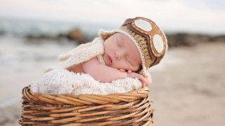 adorable baby boy sleeping in a wooden bassinet outside