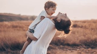 mom holds her son in her arms while standing in a meadow and laughing