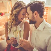 Beautiful young couple is holding glasses of champagne and smiling while celebrating at home