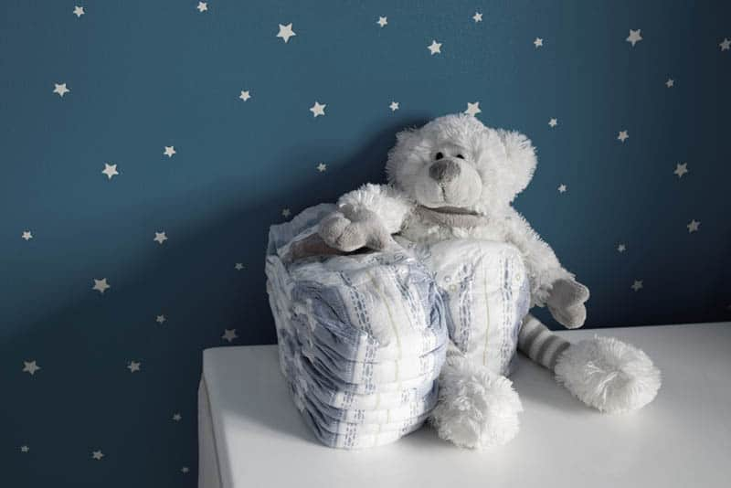 A pile of diapers and a cute baby bear on white table