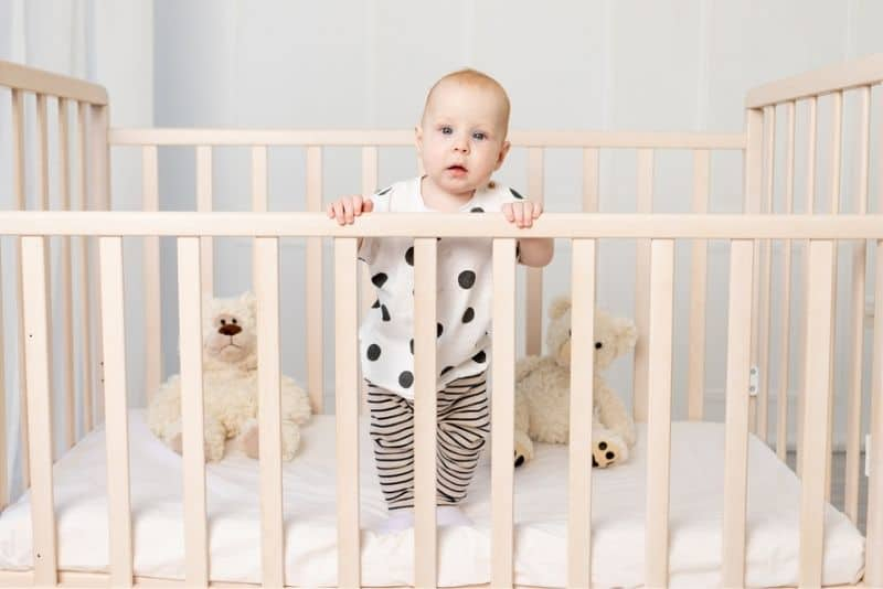 Baby in pajamas standing in crib and holding onto the rails