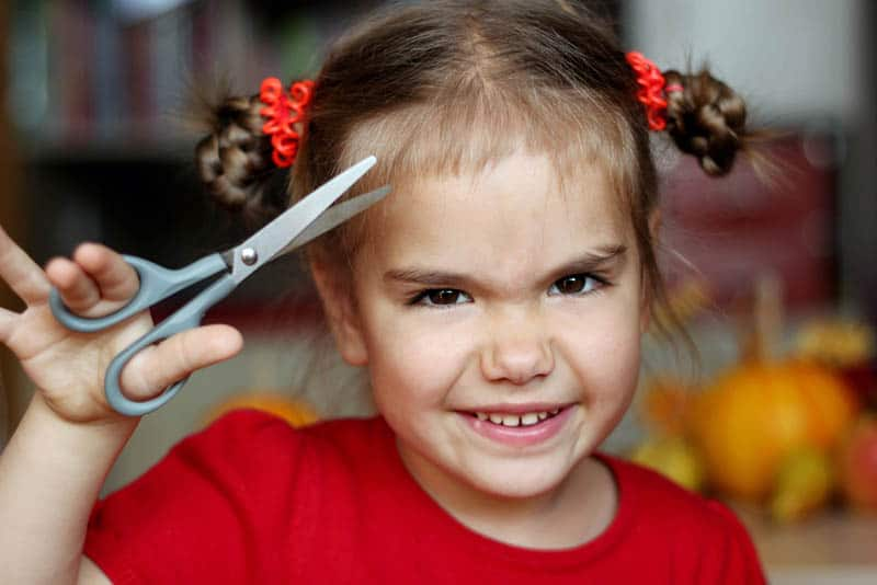 Cute little girl cutting hair to herself with scissors