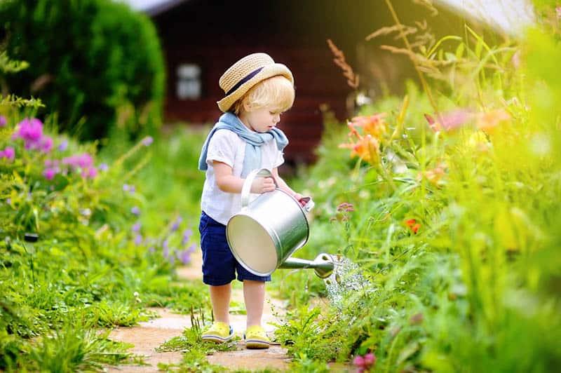 Cute toddler boy in straw hat watering plants in the garden