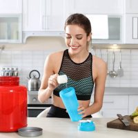 young woman preparing a pre workout drink in the kitchen before exercising