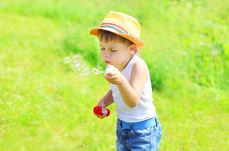 Little boy child blowing soap bubbles outdoors in sunny day