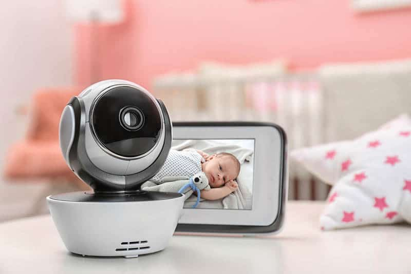 Modern security camera and monitor with baby's image on table