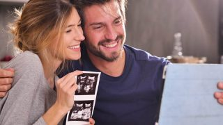 happy couple making a pregnancy announcement to parents with an ultrasound photo of their baby