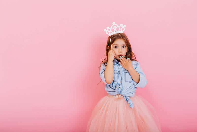 Surprised pretty young girl in tulle skirt with crown