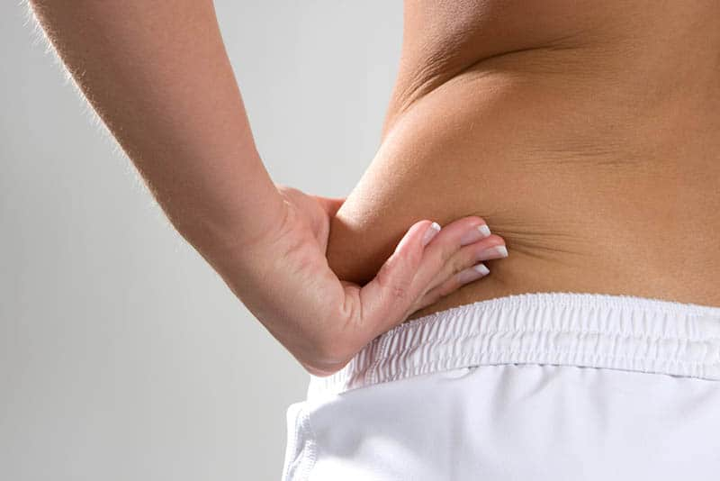 Young woman pinches the fat on the side of her wais