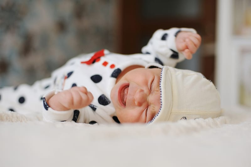 a newborn baby in sweet pijama crying on the bed