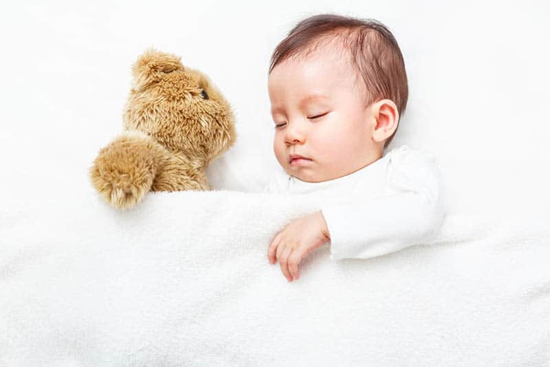 adorable baby boy sleeping in bed with teddy bear