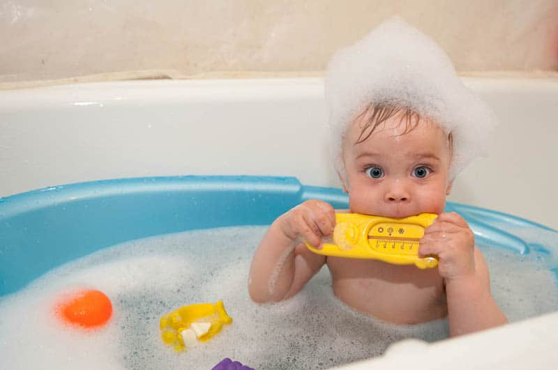 adorable baby boy taking a bath covered with bubble foam and biting a toy