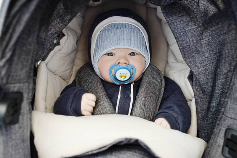 adorable baby boy with hat and winter clothes sitting in a stroller