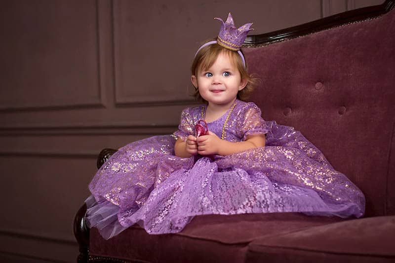 adorable baby girl dressed up as a princess sitting on the couch