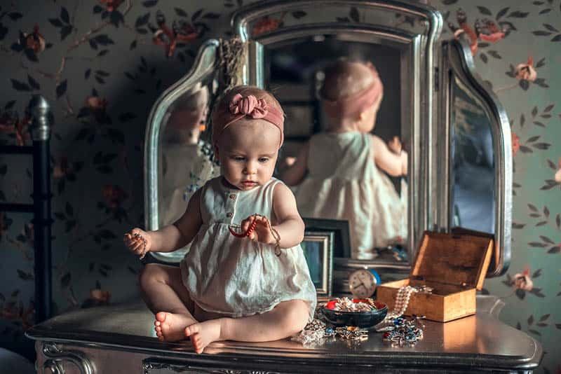 adorable baby girl playing with jewelry