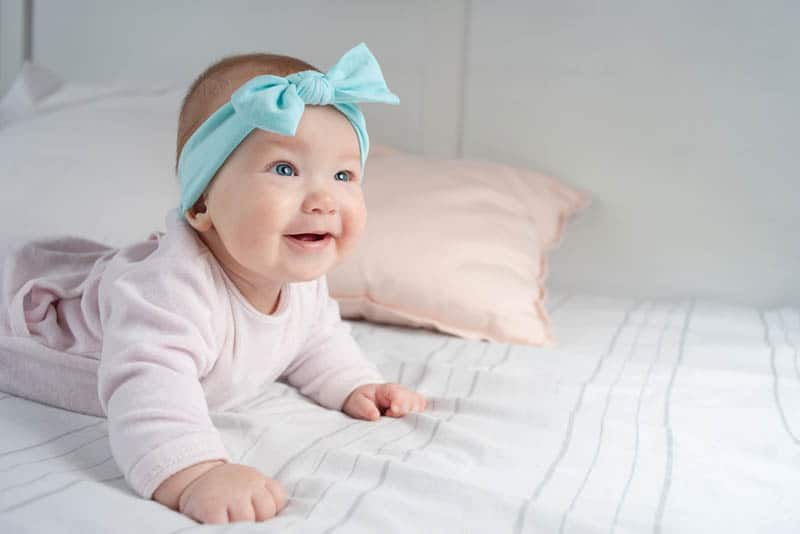 adorable baby girl wearing a blue headband and lying on the belly
