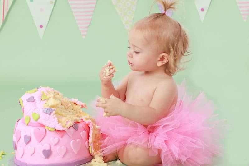 adorable baby girl wearing pink tutu skirt eating her birthday cake