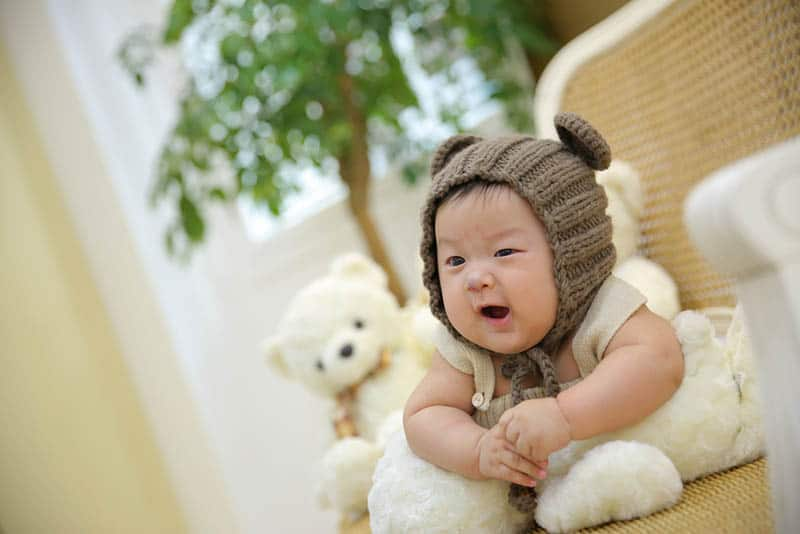 adorable baby wearing teddy hat on the floor