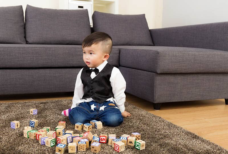 adorable little boy playing with wooden blocks on the floor