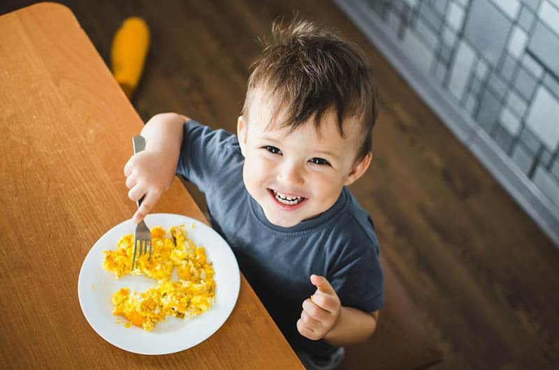 adorable little boy smiling while eating scrambled eggs
