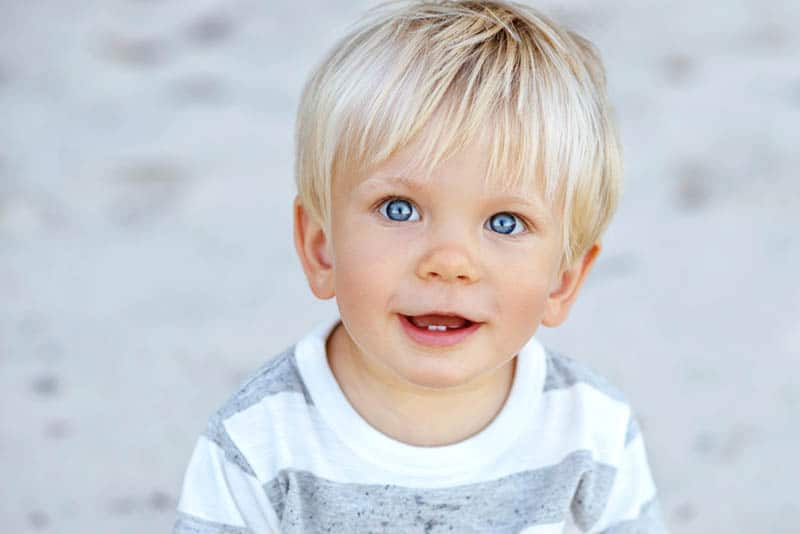adorable little boy with blue eyes and a blue hair smiling
