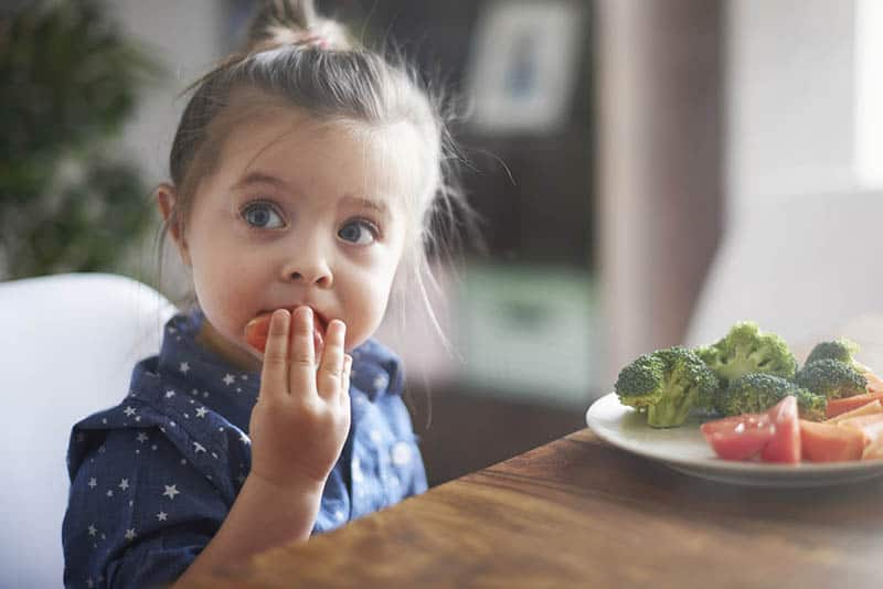 adorable little girl eating vegetables from the plate