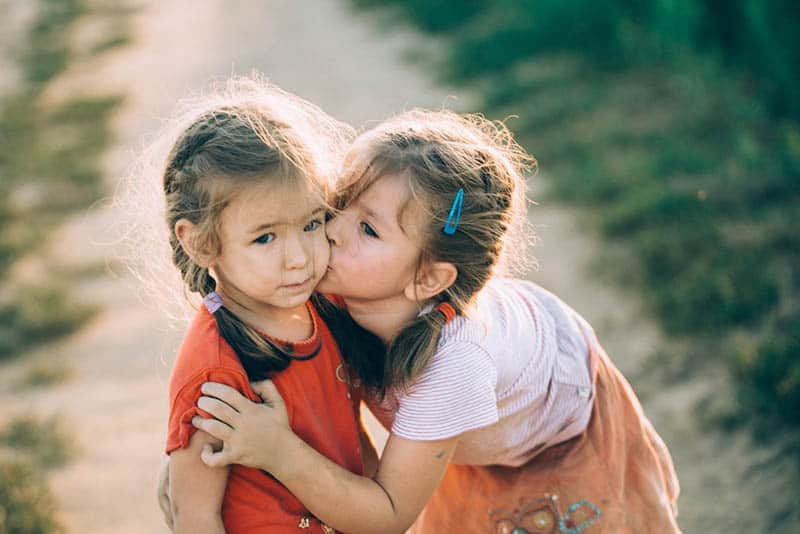 adorable little girl kissing her sister outdoor