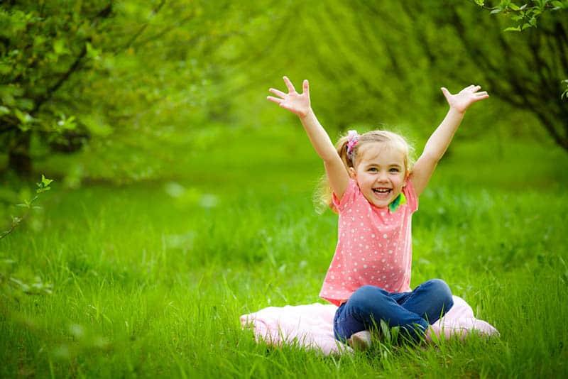 adorable little girl raising hands outdoor in the park