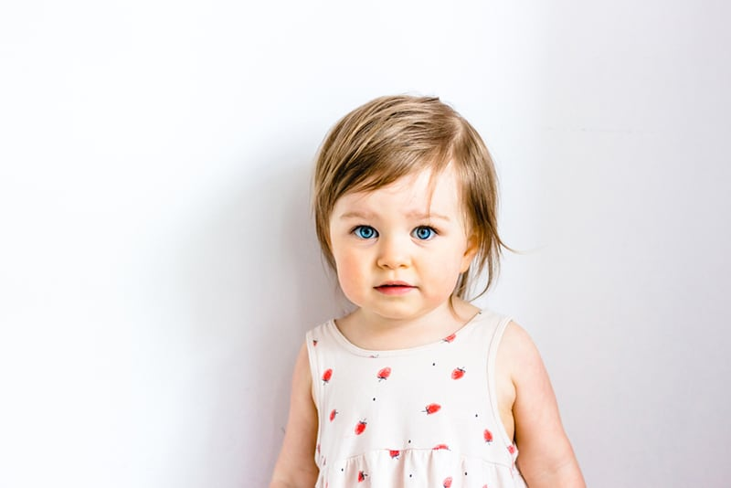 adorable little girl with short hair posing in front of white wall