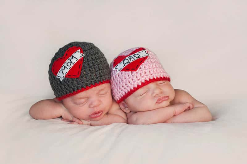 adorable twin babies sleeping with knitted hats on heads