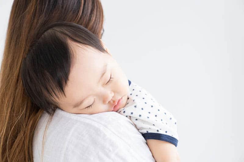 baby boy sleeping on mother's shoulder
