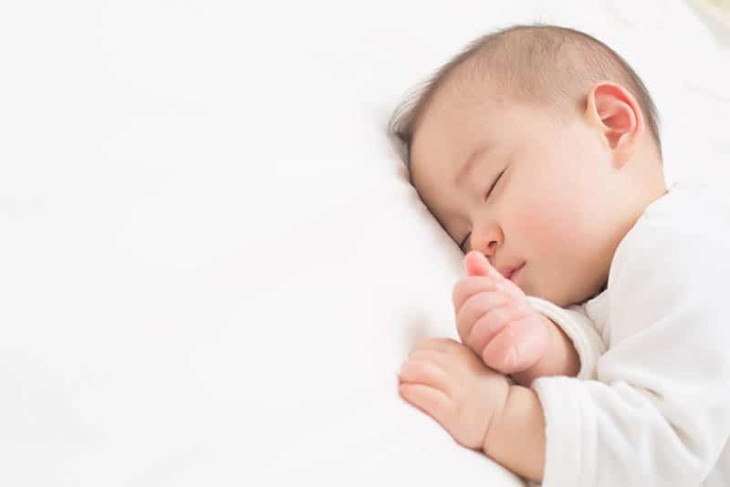 baby boy sleeping tight on white sheet