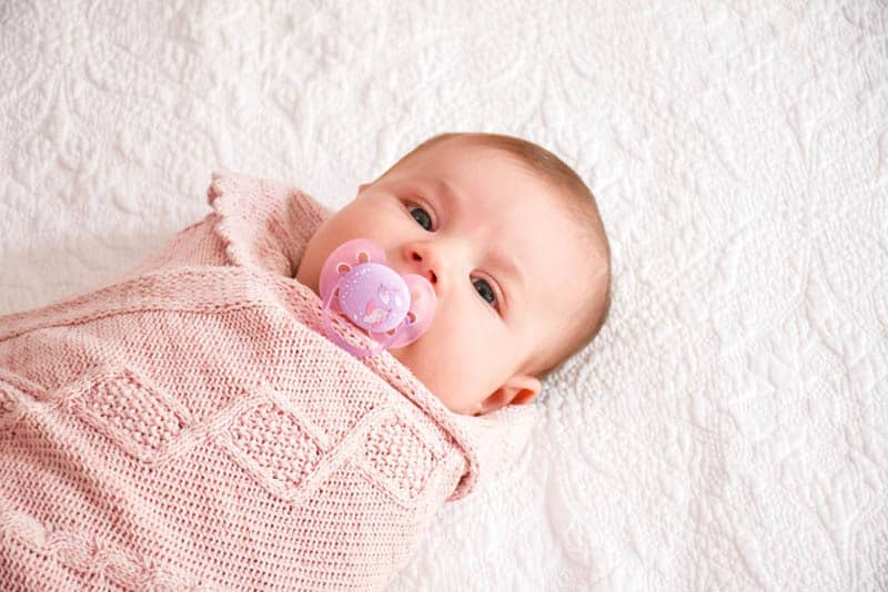baby girl swaddled in pink cloth with pacifier in mouth