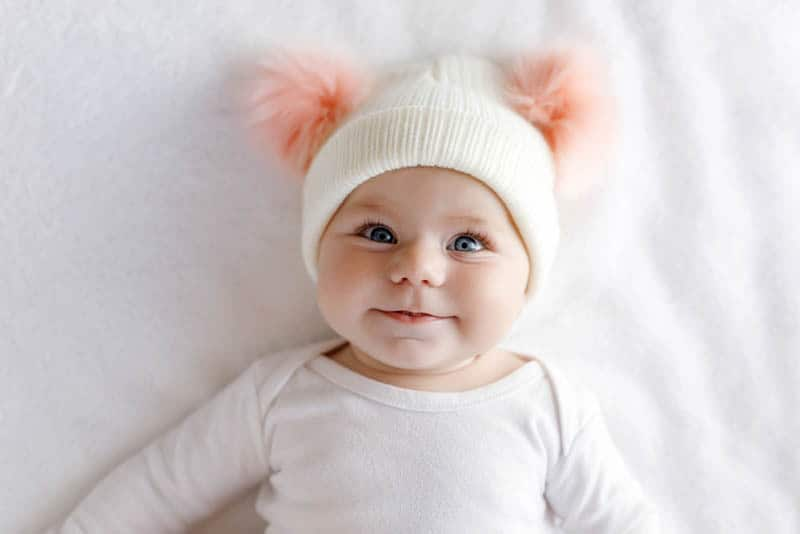 baby girl wearing hat with interesting bobbles on the bed