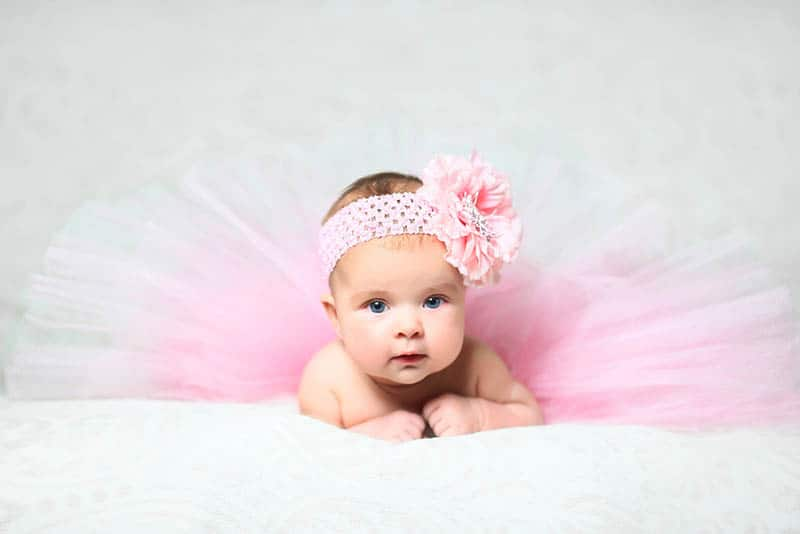 baby girl wearing pink headband and skirt and lying on the tummy