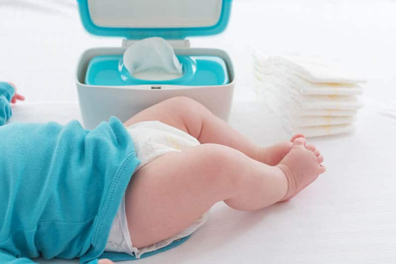 baby lying on the bed with wipes and diapers