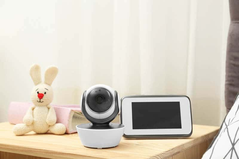 baby monitor and camera with bunny toy on the wooden table