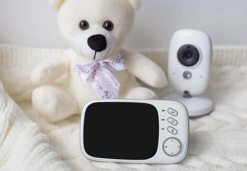 baby monitor and camera with teddy bear on blanket
