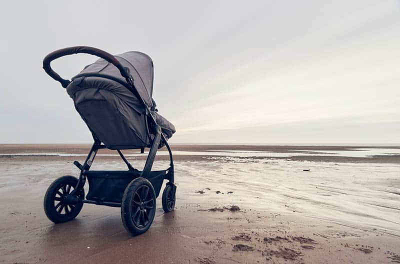 baby strollers in the sand on the beach