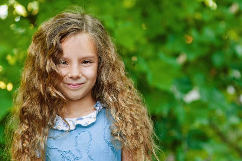 beautiful little girl with curly hair posing outdoor