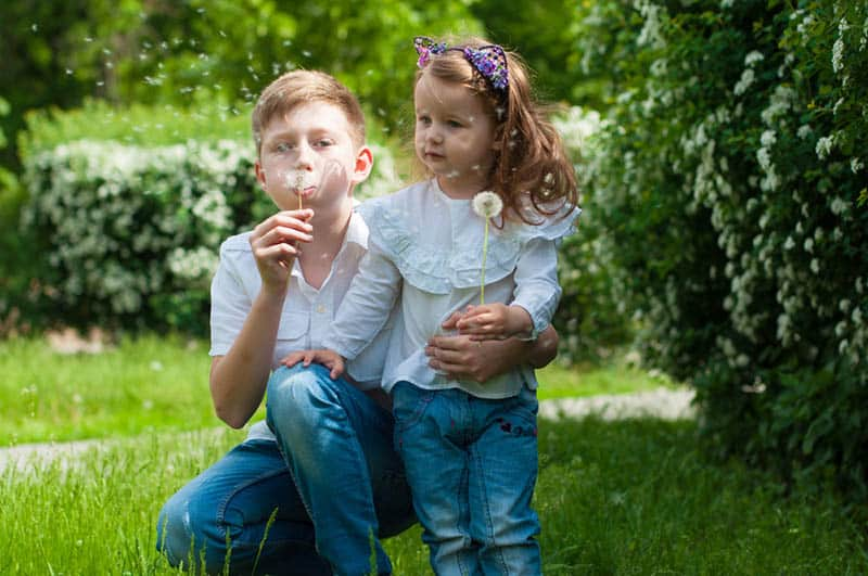 brother and little sister playing with dandelions in the garden