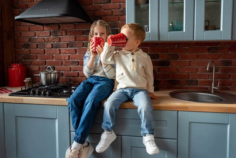 brother and sister sitting on the kitchen desk drinking hot tea